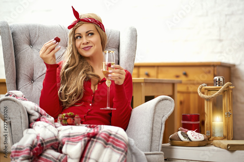 Fotografia  young smiling beautiful woman in an armchair with a glass of prosecco wrapped in
