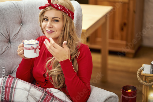 Fotografie, Obraz  young smiling beautiful woman in armchair with a cup of hot chocolate wrapped in