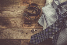 Selection Of Male Clothes - Stack Of Folded Shirts, Tie, Belt, Cufflinks, Rustic Wood Background