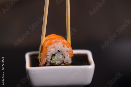 Poster Sushi bar Person dipping a fresh sushi roll in soy sauce