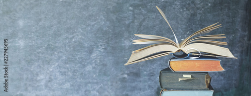 Open Book on a stack of old books in front of a blackboard