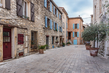 Fototapeta Narrow cobbled street with flowers in the old village Tourrettes-sur-Loup , France.