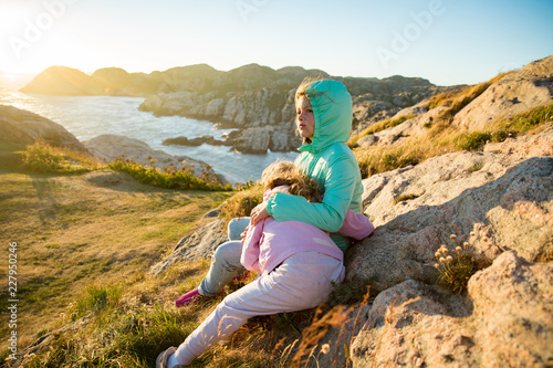 Two little girls play on rocky northern seashore Canvas Print