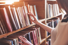 Young Attractive Student Librarian Reading A Book Between Library Bookshelves