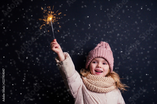 charming little girl in a knitted pink hat holding fireworks on black background in a studio Fototapeta