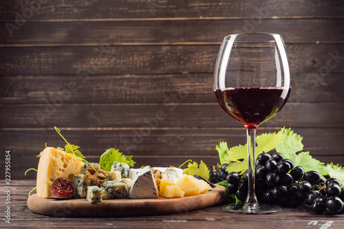 Staande foto Alcohol wine glass and bunch of grapes on wooden table