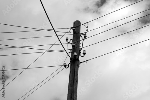 Old wooden electric pole against sky ijn black and white. Wallpaper Mural