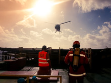Helicopter Landing Officer (HLO) And Member Of A Fire Team Receiving Landing Helicopter On A Offshore Drilling Rig