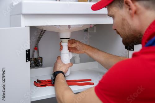 Fotografie, Tablou  plumber installing sink siphon in domestic bathroom