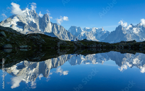 Cadres-photo bureau Reflexion Hiker at his tent in the Mont Blanc massif reflected in Lac de Chesery. Chamonix, France.