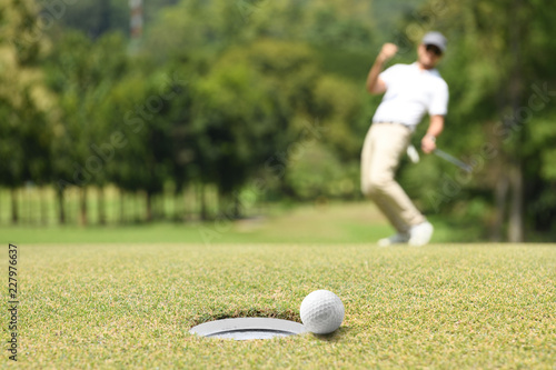 Man golfer cheering after a golf ball on a golf green