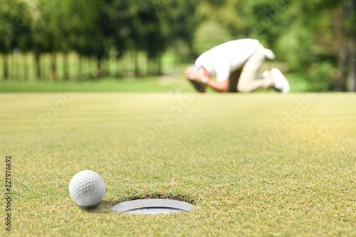 Vászonkép Man golfer feeling disappointed after a putted golf ball missed the hole