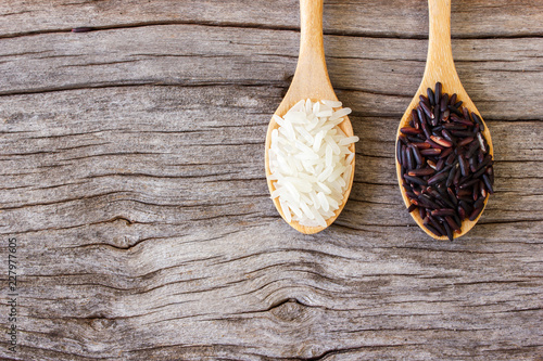 Uncooked jasmine rice and riceberry in small wooden spoon. On wooden background. Top view with copy space.