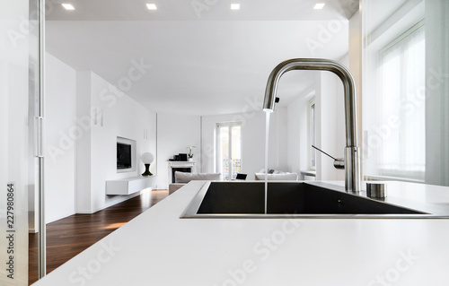 Fotografía  modern kitchen interiors in the foreground the integrated steel sink and the chr