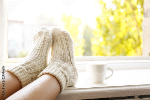 Obraz Young woman sitting with crossed legs in warm woolen socks leaning on windowsill, cup of coffee and book, autumnal window view w/ yellow leaves. November mood concept. Background, copy space, close up - fototapety do salonu