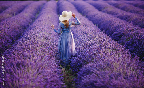 Foto op Canvas Snoeien Woman in lavender flowers field at sunset in purple dress. France, Provence.
