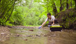 canvas print picture - Woman scientist environmentalist sitting near the creek. She taking sample of water