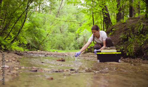 Fotografia  Woman scientist environmentalist sitting near the creek