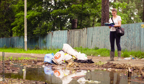 Fotografie, Obraz  Woman scientist environmentalist standing near garbage dump and making notes in