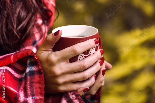 cup of herbal tea in woman hands. Autumn fall close up