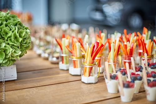 Fotografia Tasty appetizers served in glass jars on wooden table.