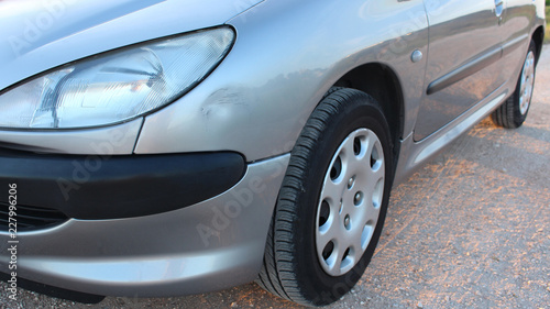 Fotografie, Obraz Silver gray car with small dent and scratches on side