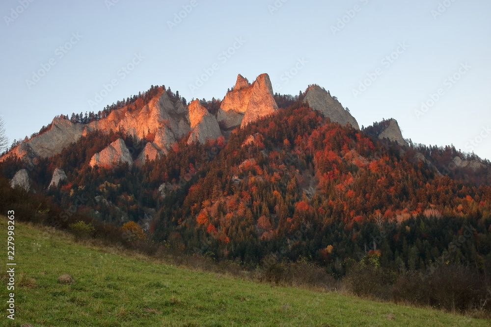 Three Crowns massive in Pieniny Mountains, Poland, view from valley in Sromowce Niżne, evening sunlight, blue sky, autumn season, colorful trees cover hill.