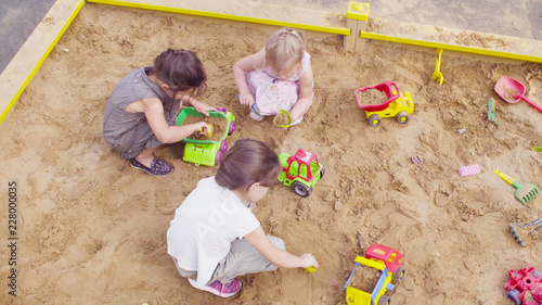 Top view. Three girls sitting in a sandbox and playing sand Canvas Print