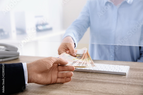 Fototapeta Man receiving money from teller at cash department window, closeup obraz
