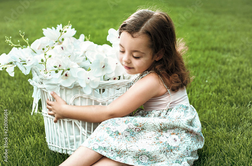 Foto op Canvas Artist KB Cute little girl holding a basket full of flowers