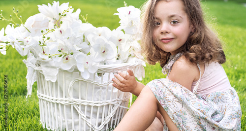 Foto op Canvas Artist KB Portrait of a cute child holding a wicker basket with white flowers