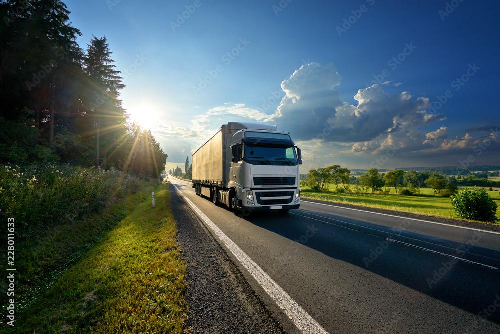 Fototapeta White truck arriving on the asphalt road in rural landscape in the rays of the sunset
