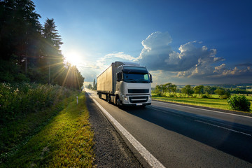 White truck arriving on the asphalt road in rural landscape in the rays of the sunset
