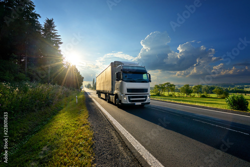 Fotografía  White truck arriving on the asphalt road in rural landscape in the rays of the s