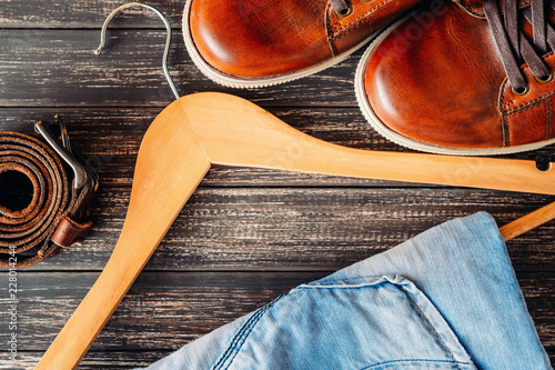 Fotografía  Brown leather casual shoes, jeans on hangerand belt on a wooden background top view