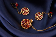 Ruby Necklace And Earrings On Blue Silk Background With Copy Space. Beautiful Precious Women's Gold Jewelry, Close-up.