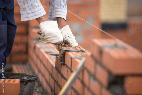 Tablou Canvas A builder lays bricks wall on a rope with trowel