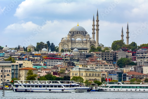 Aluminium Prints Turkey Touristic landmarks from sea voyage on Bosphorus. Cityscape of Istanbul at sunset - old mosque and turkish steamboats, view on Golden Horn.