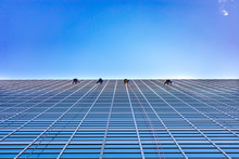 Four Window Washers Cleaning On The Side Of A Skyscraper Looking Up
