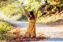 Young Pretty Woman Playing With Leaves In A Park At Autumn Day