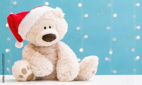 Obraz na plátně  Teddy bear wearing a Santa hat on a shiny light blue background