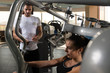 Woman With Personal Trainer At Chest In Gym