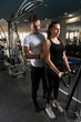 Woman With Personal Trainer At Biceps In Gym