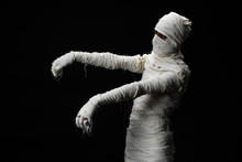 Studio Shot Portrait  Of Young Man In Costume  Dressed As A Halloween  Cosplay Of Scary Mummy Pose Like A Zombie Acting On Isolated Black Background.