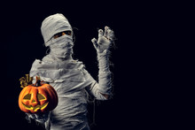 Studio Shot Portrait  Of Young Man In Costume  Dressed As A Halloween  Cosplay Of Scary Mummy Pose Like A Hold Jack'o Pumpkin Clamber Acting On Isolated Black Background.