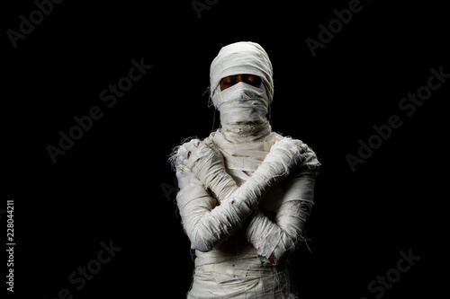 Carta da parati Studio shot portrait  of young man in costume  dressed as a halloween  cosplay of scary mummy pose like close eye and cross his arm acting standing on isolated black background