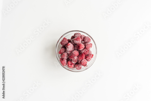 Directly above view of frozen raspberries in glass bowl on white background