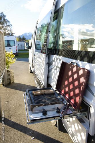 Slika na platnu Using a built in barbeque on the side of a campervan