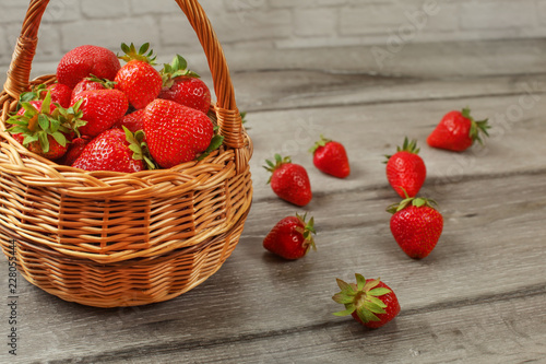 Fotografering  Basket with strawberries, some of them spilled on gray wood desk.