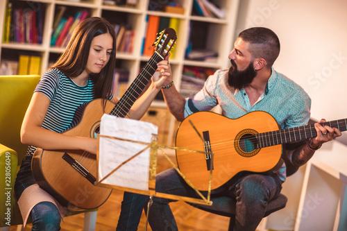 Guitar teacher teaching the girl at home. Canvas Print